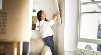 Woman taking a canvas art off the wall ready to pack while moving house